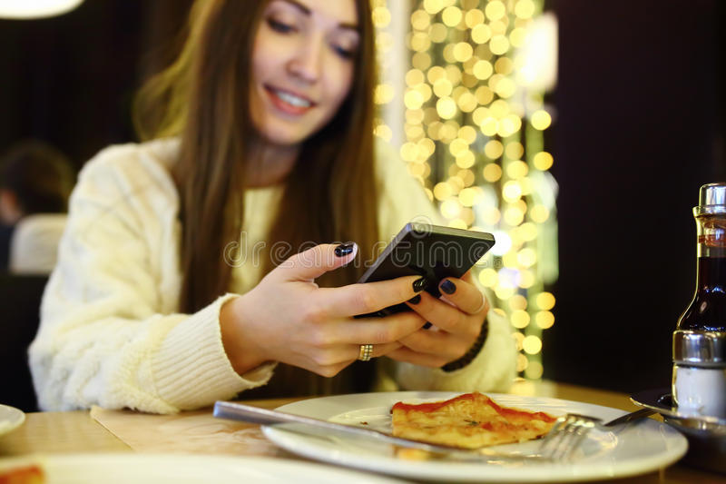 Vrouw het typen schrijft bericht op slimme telefoon in een moderne koffie Bebouwd beeld van jonge mooie meisjeszitting bij een li stock afbeeldingen