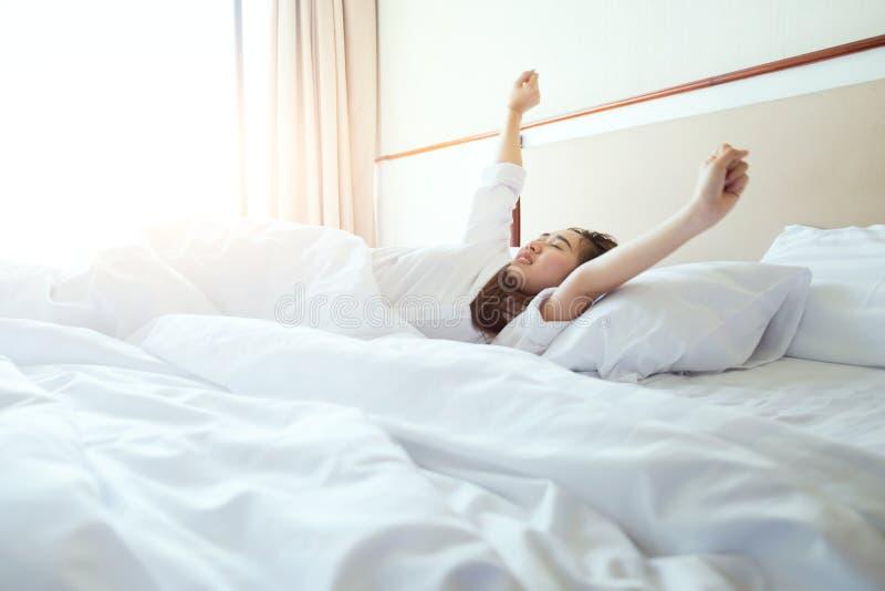 Vrouw het uitrekken zich in bed na ontwaken, zonlicht in ochtend stock fotografie
