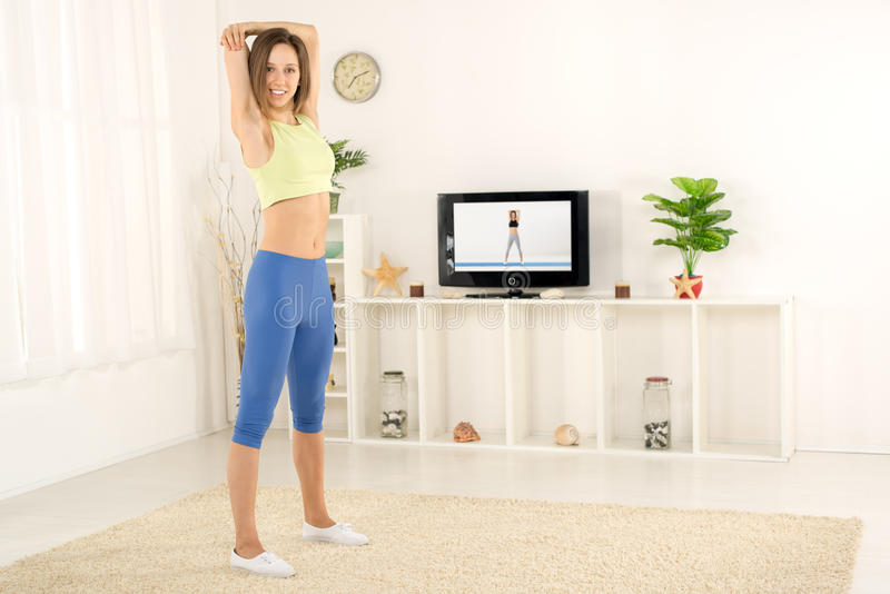 Vrouw het Uitrekken zich in Front Of-TV stock fotografie