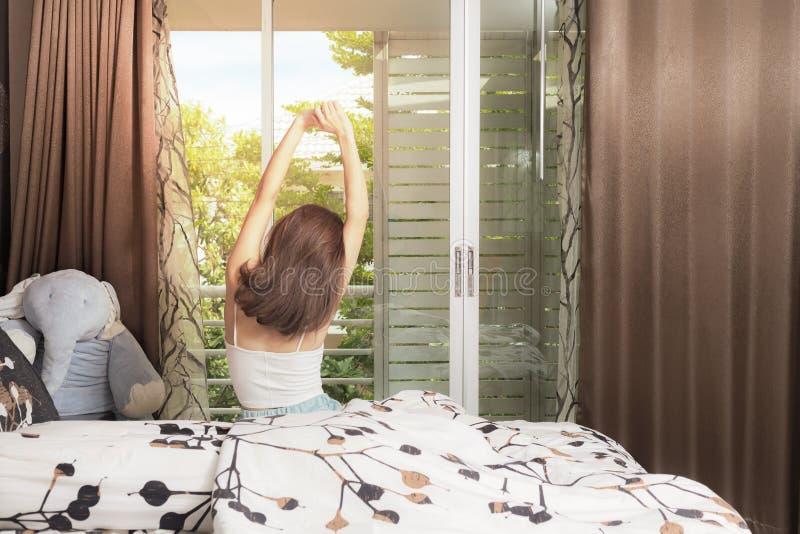 Vrouw het uitrekken zich op bed na kielzog omhoog, achtermening royalty-vrije stock fotografie