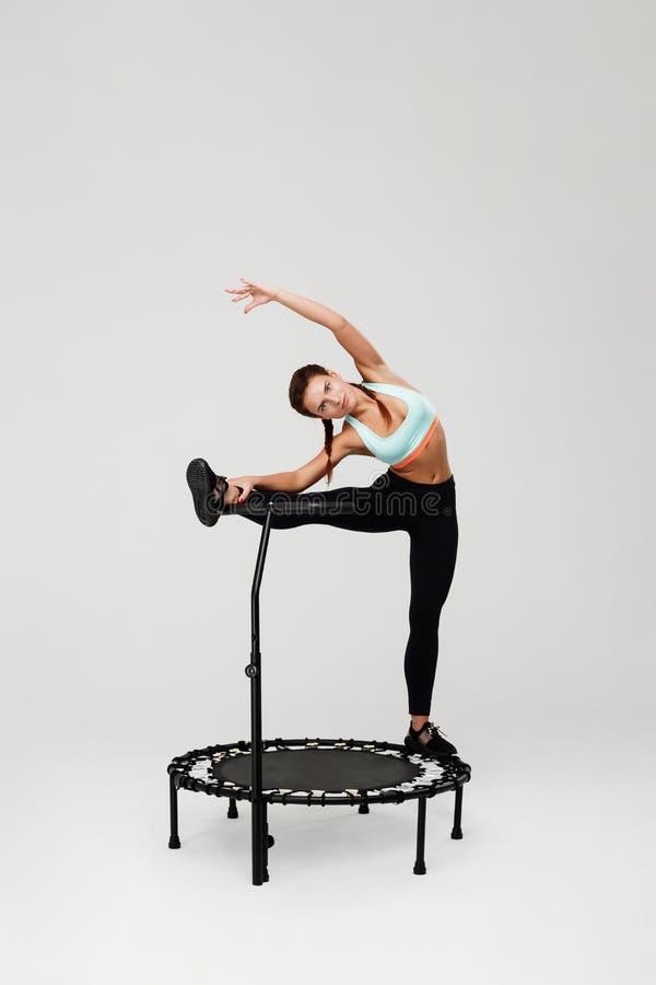 Vrouw het uitrekken zich spieren die op rebounder met been op handvat blijven stock afbeeldingen
