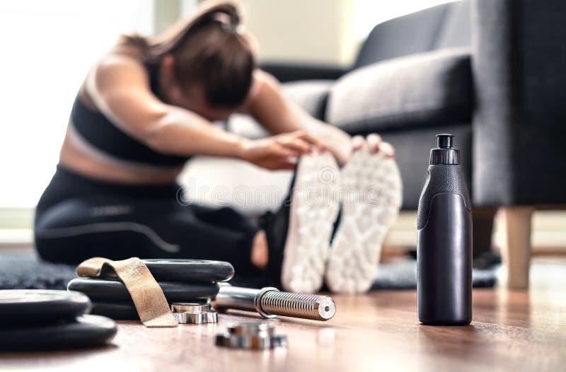 Vrouw het uitrekken zich spieren vóór gymnastiektraining en gewichtheffen in huiswoonkamer Vrouwelijke geschiktheidsatleet die op royalty-vrije stock foto's