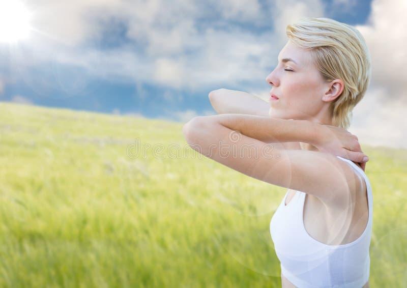 Vrouw het uitrekken zich tegen onscherpe weide op de zomerdag met gloed stock foto