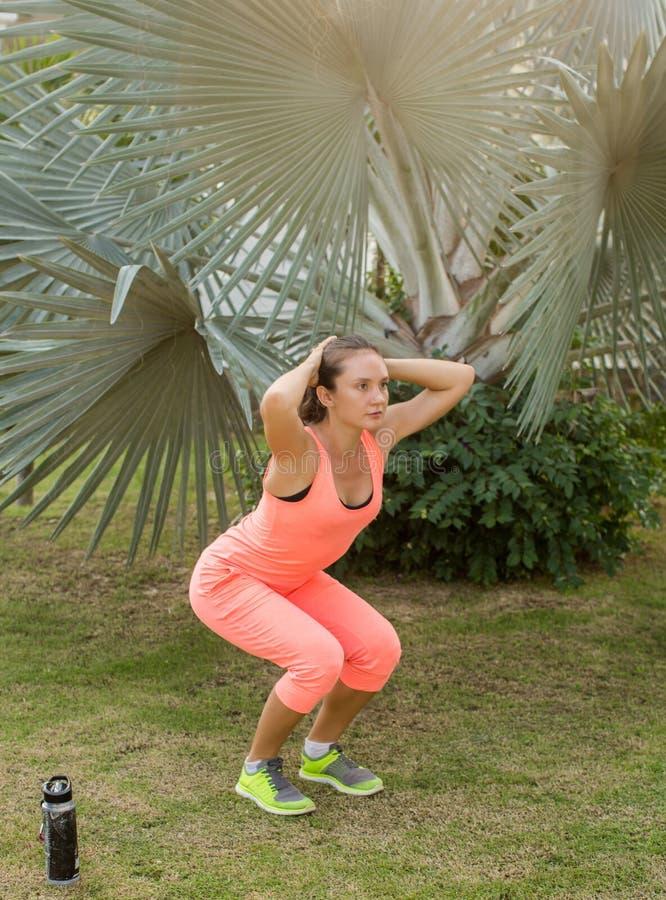 Vrouw het uitrekken zich vóór haar training stock afbeelding
