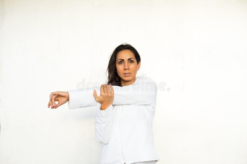 Vrouw het uitrekken zich wapen en schouder royalty-vrije stock foto