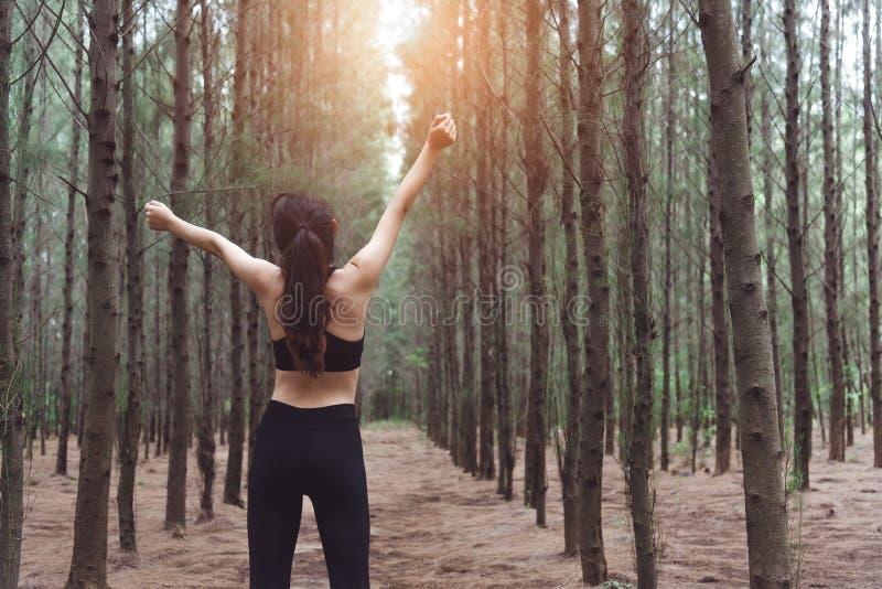 Vrouw het uitrekken zich wapens en ademhalings verse lucht in midden van pinew stock foto