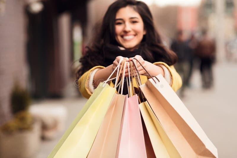 Vrouw het uitrekken zich het winkelen zakken aan camera, close-up stock afbeeldingen