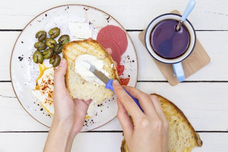 Vrouw het uitspreiden boter op geroosterd brood bij ontbijtlijst royalty-vrije stock foto