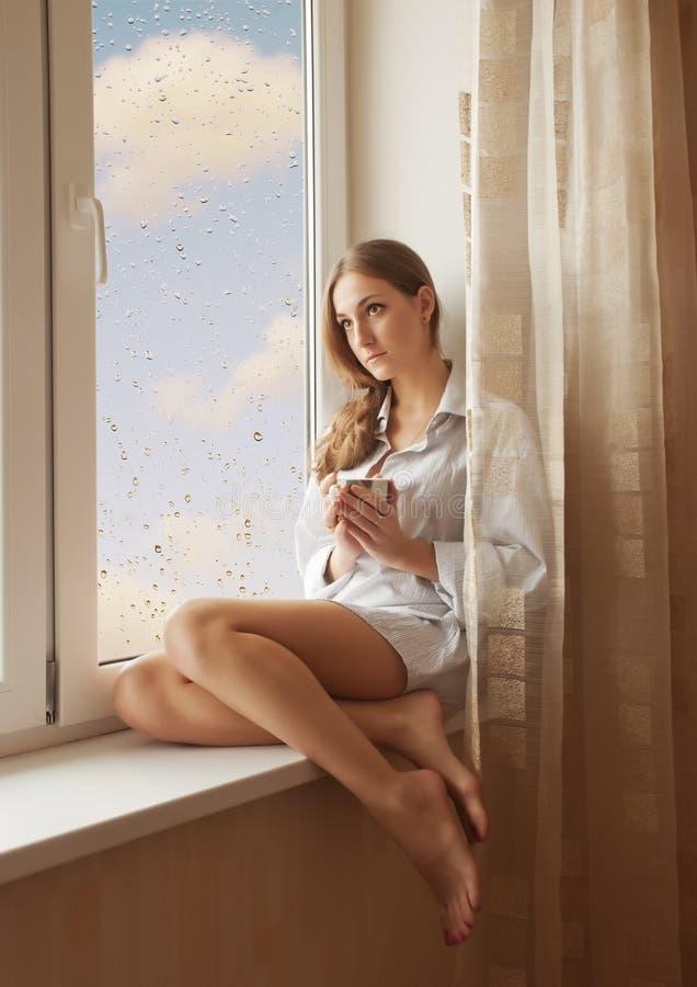 Vrouw in het venster stock foto