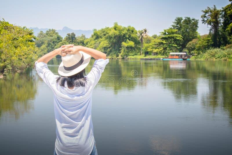 Vrouw het verheugen zich op rivier met zette haar handen op hoofd en zij heeft het voelen ontspannen en geluk royalty-vrije stock afbeeldingen