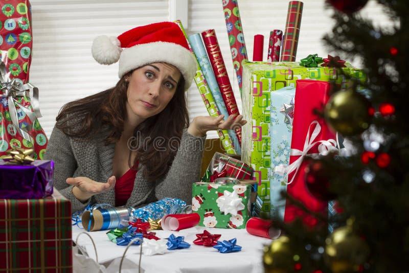 Vrouw het verpakken Kerstmis stelt voor, kijkend uitgeput stock afbeelding