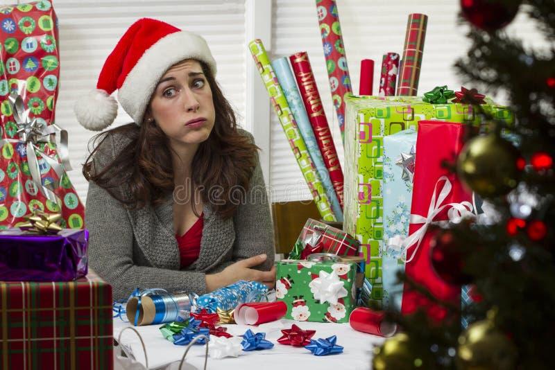 Vrouw het verpakken Kerstmis stelt voor, kijkend uitgeput stock fotografie
