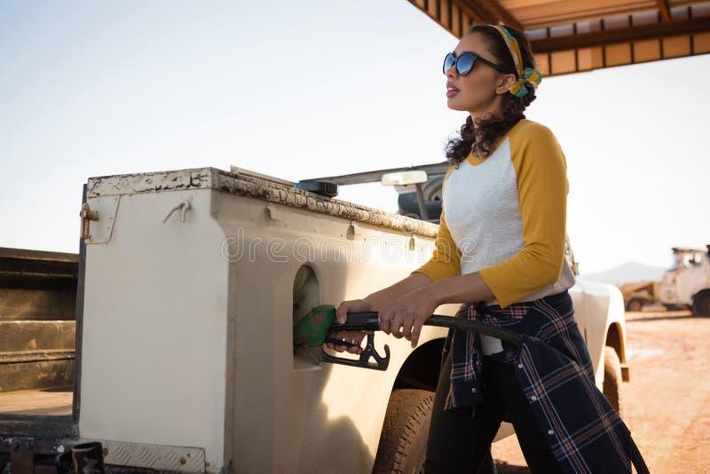Vrouw het vullen benzine in auto bij benzinepomp stock foto