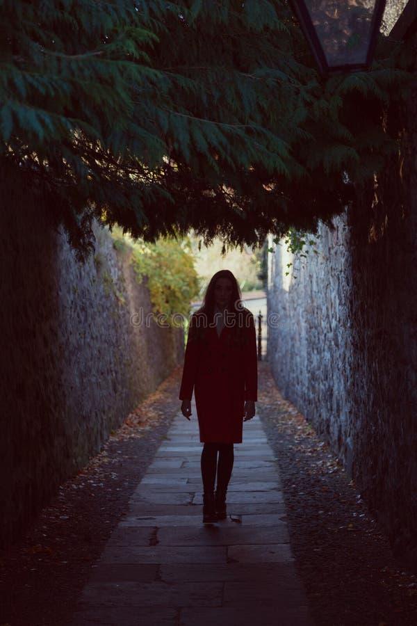 Vrouw het waling weg onderaan een donkere steeg royalty-vrije stock afbeeldingen