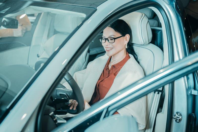 Vrouw het wennen aan zit in haar nieuwe auto stock foto's