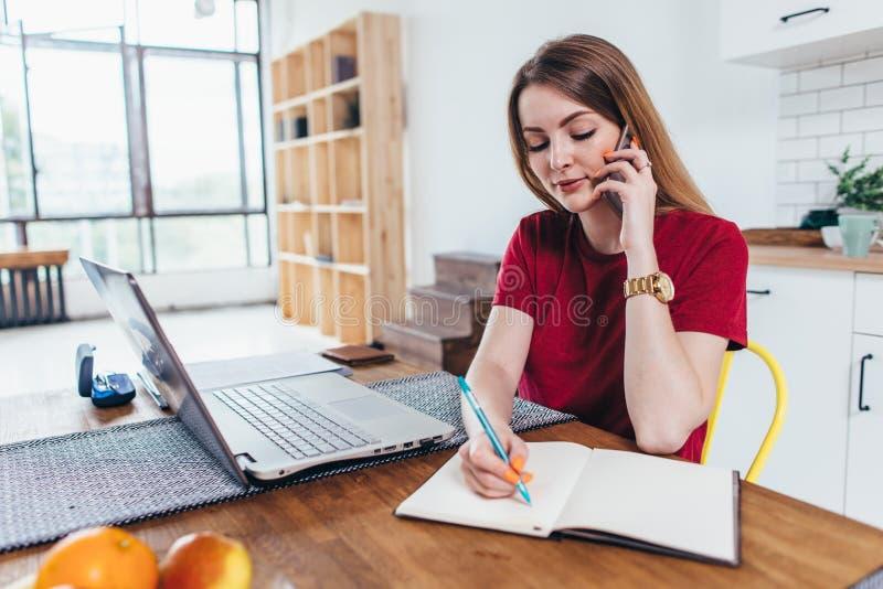 Vrouw het werken thuis schrijft nota's terwijl het spreken op telefoon royalty-vrije stock fotografie