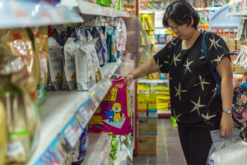 Vrouw het winkelen toebehoren of voedsel voor huisdieren in petshop stock foto's