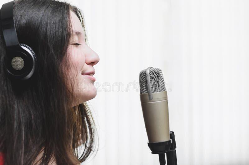 Vrouw het zingen bij een studiomicrofoon, die een hoofdtelefoon dragen royalty-vrije stock fotografie