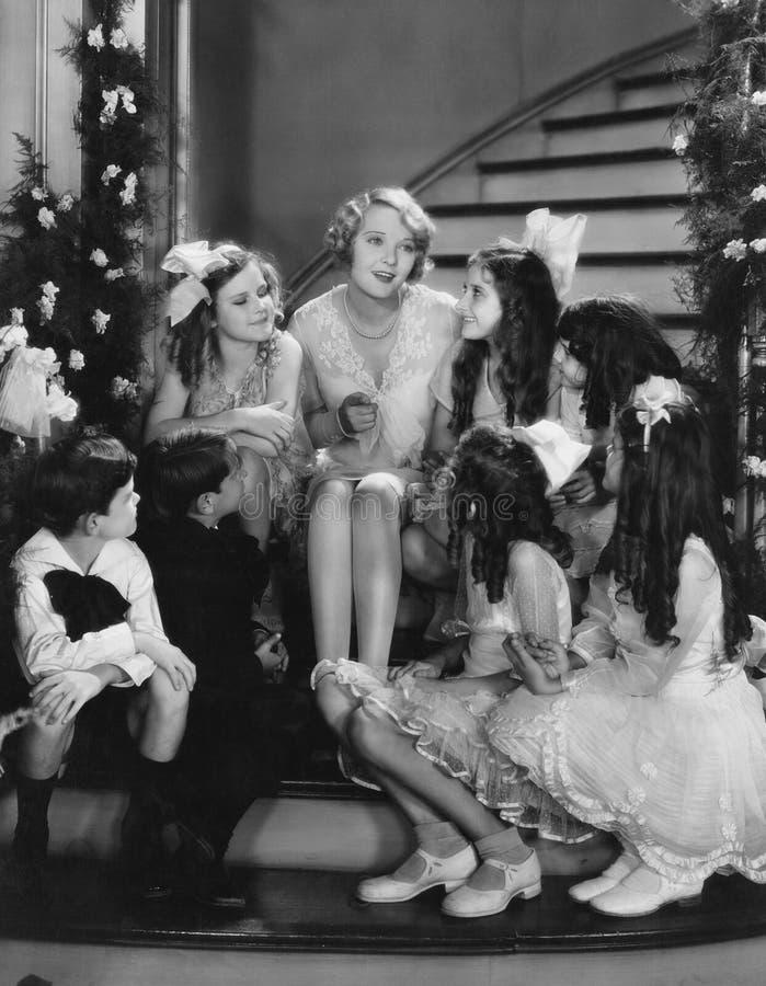 Vrouw het zingen met kinderen op trap bij Kerstmis (Alle afgeschilderde personen leven niet langer en geen landgoed bestaat lever royalty-vrije stock foto's