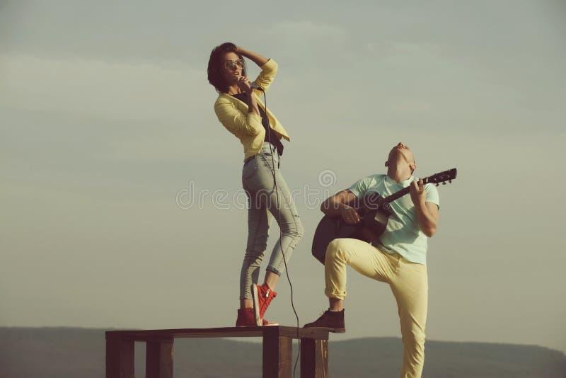 Vrouw het zingen op lijst en knappe man het spelen gitaar royalty-vrije stock afbeelding