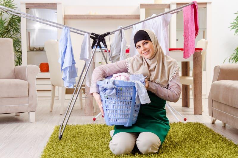 Vrouw in hijab die kleding doen die thuis strijken stock afbeelding