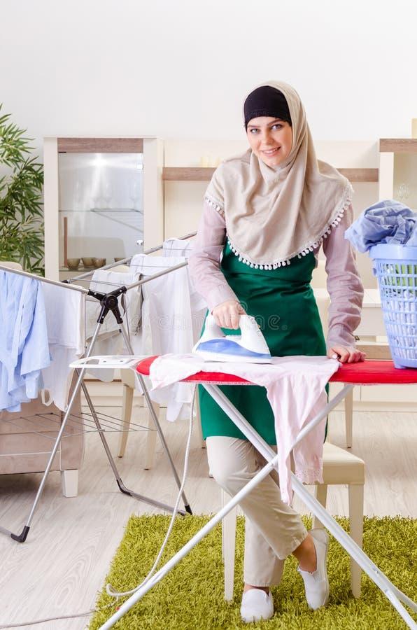 Vrouw in hijab die kleding doen die thuis strijken royalty-vrije stock foto's