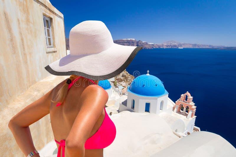 Vrouw in hoed bij mooie Oia stad van Santorini-eiland in Griekenland stock foto's