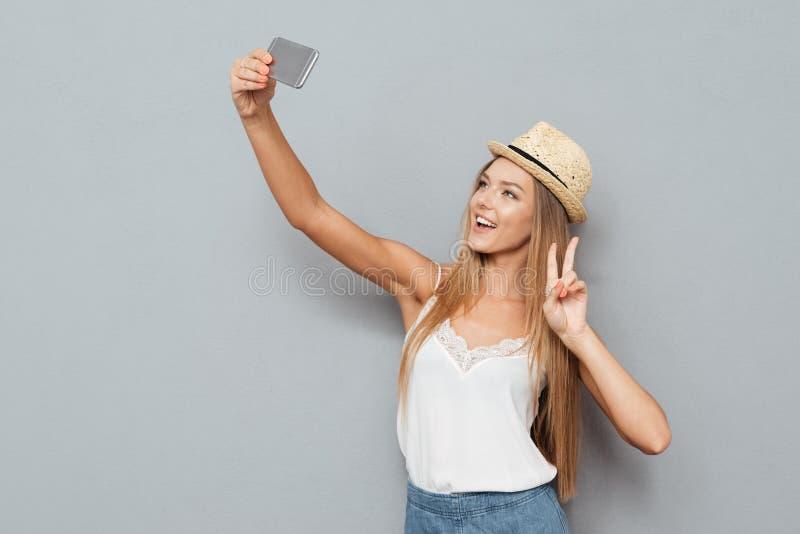 Vrouw in hoed die selfie foto maken en vredesgebaar tonen stock foto's