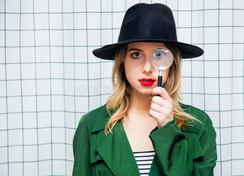 Vrouw in hoed en groene mantel in jaren '90stijl met magnifie royalty-vrije stock foto's