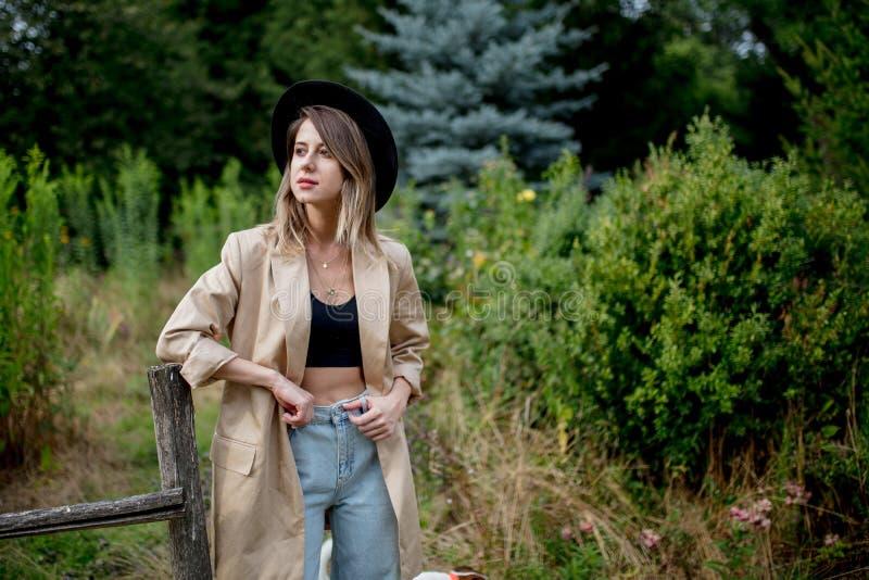 Vrouw in hoed en jasje in oude plattelandstuin stock afbeeldingen