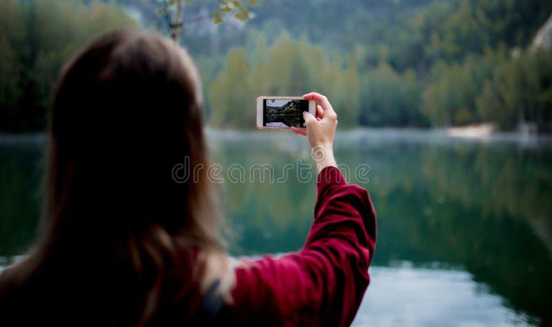 Vrouw in hoed en rood overhemd met mobiele telefoon dichtbij meer stock afbeeldingen