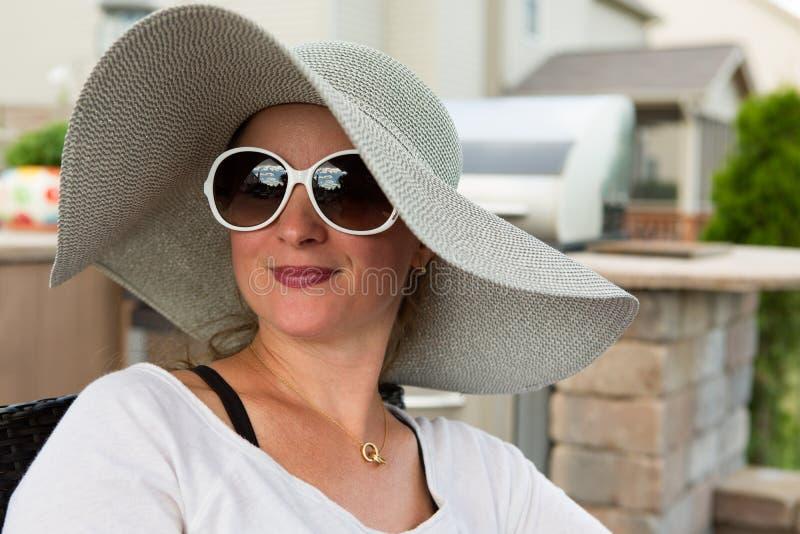 Vrouw in Hoed en Zonnebril die op Achterterras zitten stock foto