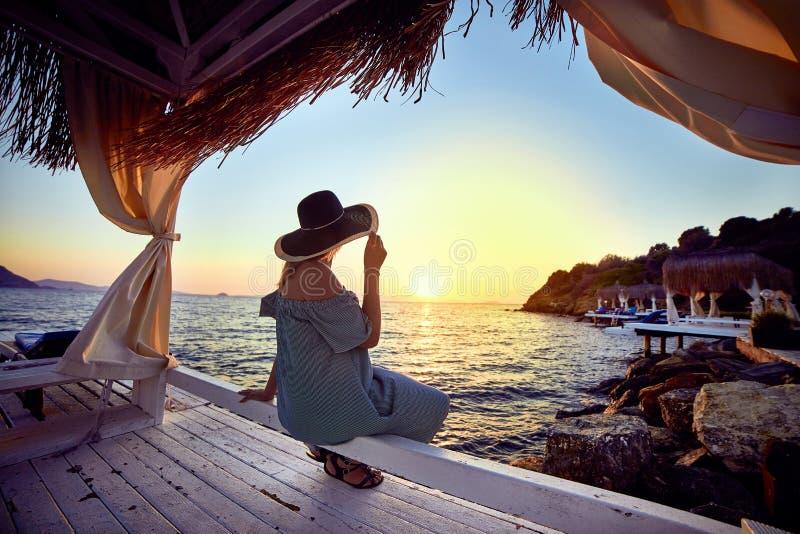 Vrouw in hoed het ontspannen door het overzees in een luxueuze toevlucht van het beachfronthotel bij zonsondergang die van de per royalty-vrije stock afbeeldingen