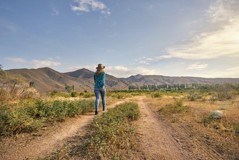 Vrouw in hoed op de landweg stock afbeeldingen