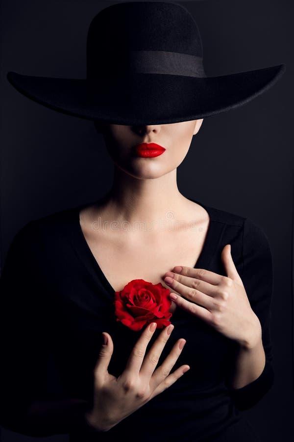 Vrouw in Hoed, Rose Flower op Hart, Elegante Mannequin Beauty Portrait op Zwarte, Rode Lippen Verborgen Ogen royalty-vrije stock fotografie