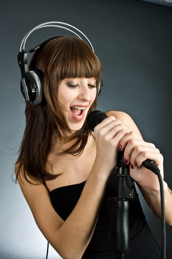 Vrouw in hoofdtelefoons die in Microfoon zingen stock foto