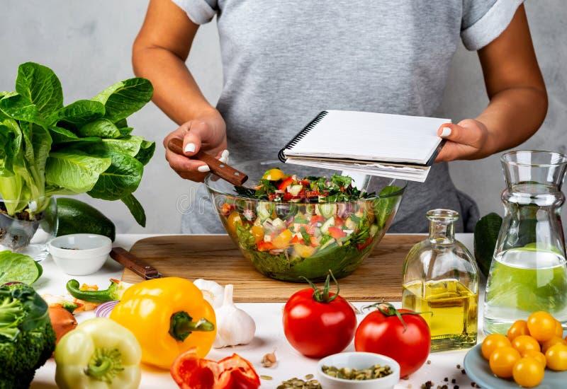 Vrouw houdt een recept-boek met ruimte voor tekst in haar hand en koelt gezond voedsel in de keuken Gezonde vegaanvoeding royalty-vrije stock fotografie