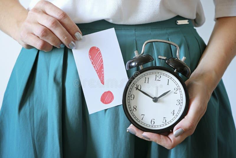 Vrouw houdt klok vast op buik Gemiste periode, ongewenste zwangerschap, gezondheid van vrouwen en vertraging in menstruatie stock fotografie