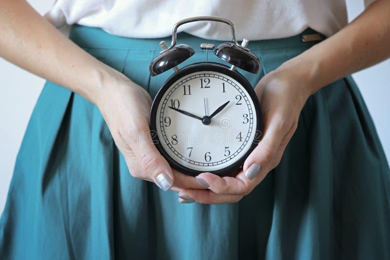 Vrouw houdt klok vast op buik Gemiste periode, ongewenste zwangerschap, gezondheid van vrouwen en vertraging in menstruatie stock foto