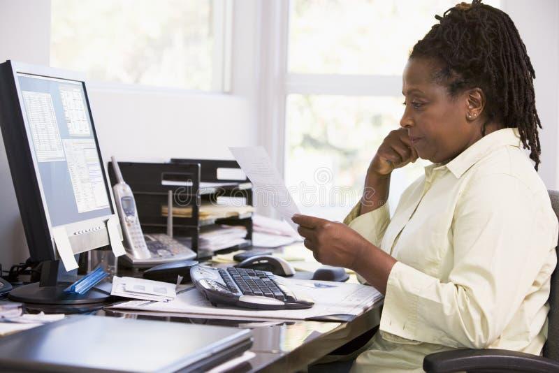Vrouw in huisbureau dat computer met behulp van