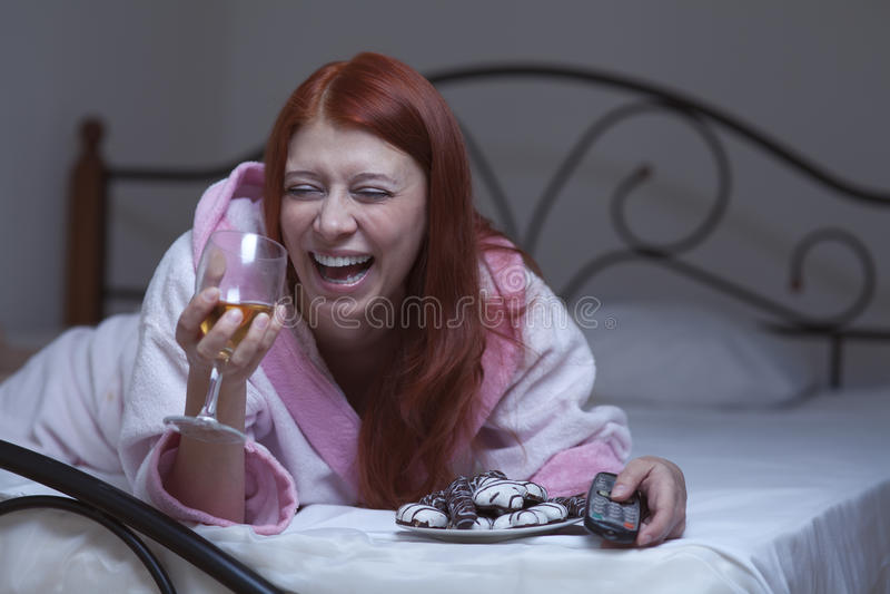Vrouw in hysterische TV van het depressiehorloge met wijn royalty-vrije stock afbeelding