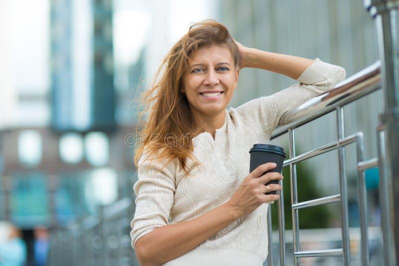 Vrouw 30 jaar het oude lopen in de stad op een zonnige dag met een kop royalty-vrije stock afbeeldingen