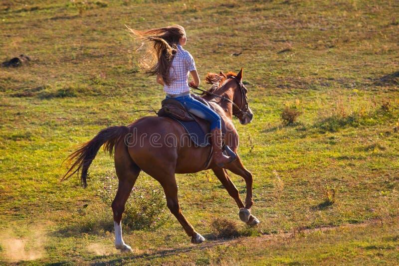 Vrouw in jeans die een paard berijden royalty-vrije stock afbeelding
