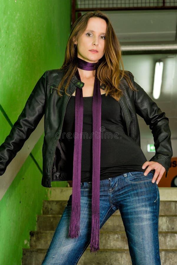 In Vrouw in jeans die in grungy ondergronds stellen royalty-vrije stock afbeeldingen