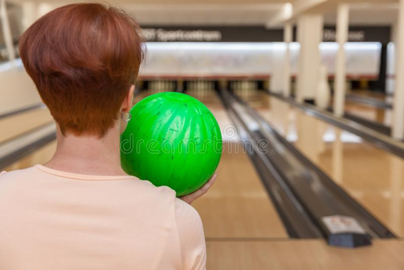 Vrouw in kegelenclub met bal in hand klaar om staking te spelen stock fotografie