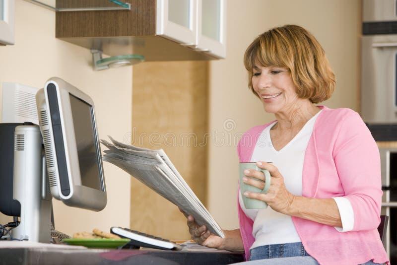 Vrouw in keuken met krant en koffie het glimlachen stock afbeeldingen