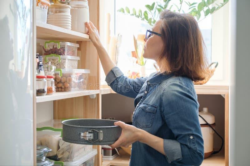 Vrouw in keukenvoorraadkast Opslag houten tribune met keukengerei, producten noodzakelijk te koken stock afbeelding