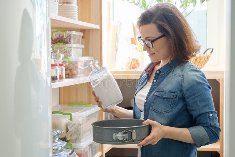Vrouw in keukenvoorraadkast Opslag houten tribune met keukengerei, producten noodzakelijk te koken stock foto