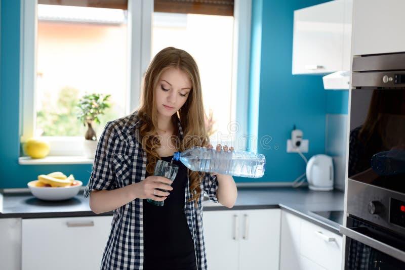Vrouw in keukenvrouw die een glas water gieten royalty-vrije stock afbeelding