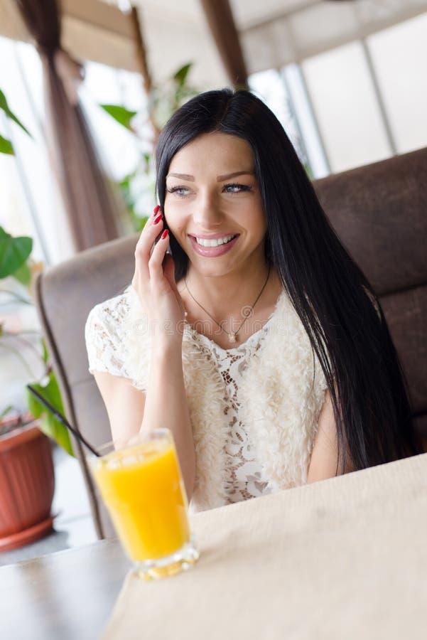 Vrouw in koffie het drinken jus d'orange, het glimlachen het spreken op mobiel stock foto's